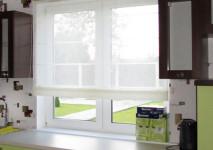 римская штора из испанкой льняной гардины на кухонное окно со вставкой вверху из испаской хлопковой полупарчи. полуоткрытый вид днем.