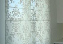 римская штора на кухню из испанской хлопковой органзы с классическим дамасским вензелем. закрытый вид днем.