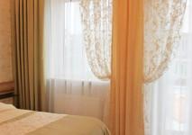 комплект штор на окно из зеленой полупарчовой портьерной ткани и вискозной гардины с рисунком. покрывало на кровать со вставкой из гардины.