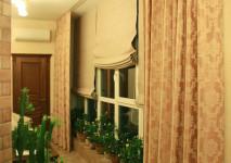 римские шторы из бельгийского блэкаута на панорамное окно. полуоткрытый вид вечером.