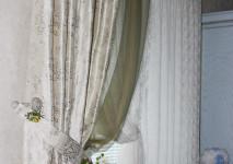 короткая портьера с классическим цветочным рисунком в подхвате на кухонное окно.