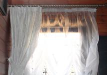 статичная австрийская штора из металлизировнной немецкой органзы белого цвета. крепление на обычный кольцевой карниз. вид шторы днем.