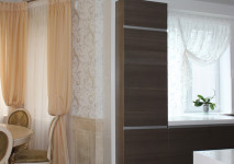 совмещенная столовая и кухня. легкие шторы в эркер для столовой и короткая гардина с вензелем на окно в кухне.