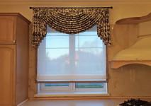 римская штора из испанкой льняной гардины на кухонное окно с узкими кантами из хлопкового испанского жаккарда. сверху мини-ламбрекен с крепелением на кольцевой карниз. вид изделия в полуоткрытом виде днем.