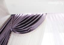 потолочный карниз в нише с подстветкой. бок фиолетовой шторы обработан стеклярусом. портьера в подхвате из ткани,закрепленном на карнизе.